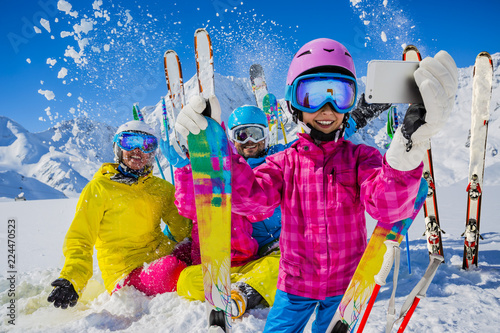 Teenager taking a selfie, girl taking a self portrait with mobile phone, sport skiing having fun on winter vacation. - 224470523