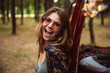 Image of excited woman 20s, wearing stylish accessories smiling while resting in forest camp