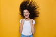 Image of excited woman with shaking hair screaming and rejoicing, isolated over yellow background