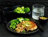 Fried pork steak with broccoli and onion sauce. - 224505902