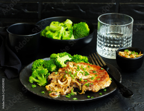 Fried pork steak with broccoli and onion sauce. - 224505902