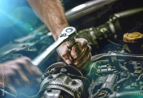 Auto mechanic working on car engine in mechanics garage. Repair service. authentic close-up shot - 224513123