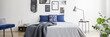 Real photo of a navy blue bedroom interior with a double bed, pillows and graphics on a wall