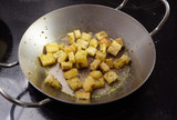 crispy croutons fried with herbs in a pan on the dark stove, cooking concept - 224564547