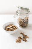 dried porcini mushrooms in a glass jar and soaked in water as preparation for cooking on a white kitchen worktop, copy space, vertical - 224565133