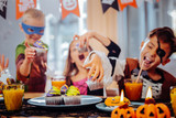 Halloween cupcakes. Emotional funny children wearing different Halloween costumes feeling very excited while taking cupcakes - 224600928