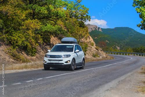 Fototapeta SUV on road in mountain district