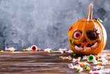 Orange pumpkin carved into Jack o Lantern with eyeball candy and gummy worms & spiders on wooden table. Background, copy space, close up, top view. Halloween party decoration. Trick or treat concept.