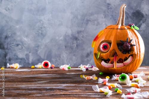 Pomarańczowa dynia wyrzeźbione w Jack o Lantern z cukierków gałki ocznej i gummy robaki i pająki na drewnianym stole. Tło, kopia przestrzeń, zbliżenie, widok z góry. Dekoracja Halloween party. Koncepcja trick or treat.