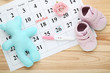 Pregnancy test with flower, soft toy and paper calendar on wooden table