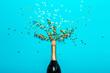 Leinwandbild Motiv Champagne bottle with colorful party streamers