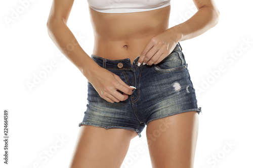 Leinwanddruck Bild A young woman unzipping her short jeans on white background