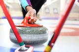 Zawodnicy grają w curling na torze curlingowym.