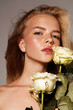 Beauty young model with white rose. Perfect glow skin. Blonde hair. Fresh look.