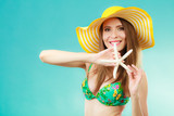 Woman in yellow hat holding white shell - 224678107