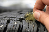 Measuring tire tread depth with two euro coin. Close up image with room for text. Shallow depth of field. - 224700314