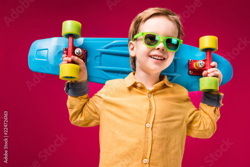 stylish smiling boy in sunglasses posing with penny board isolated on red - 224726163