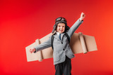 little emotional pilot in suit and cardboard plane wings with outstretched arms to fly isolated on red