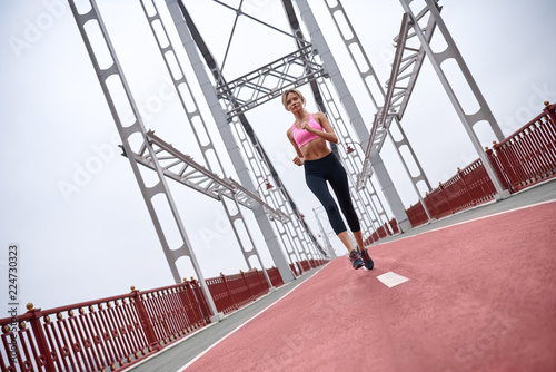 Foto Murales Morning workout. Full length rear view of young womanin sports clothing exercising while jogging on the bridge outdoors
