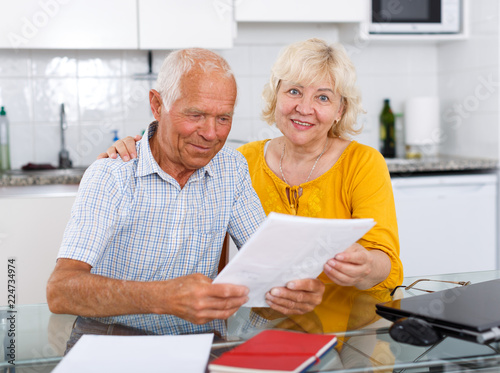Happy mature couple with documents sitting at table in home