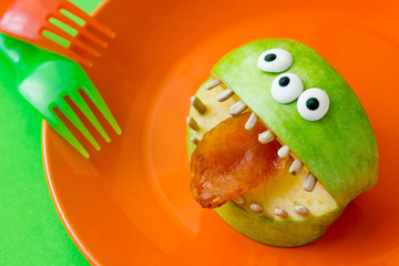 Halloween treat idea for kids - healthy monster apples with candy eyeballs, sunflower seeds teeth and dried apricot tongue