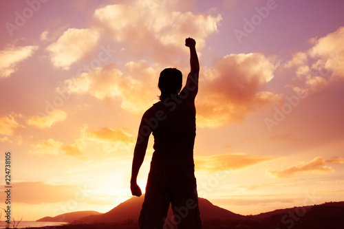 Young motivated man standing on mountain with fist in the air.