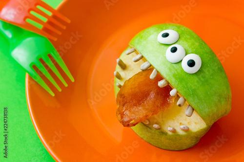 Leinwandbild Motiv Halloween treat idea for kids - healthy monster apples with candy eyeballs, sunflower seeds teeth and dried apricot tongue