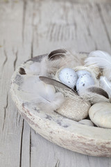 Easter decoration with eggs, feather and pebble
