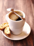 Cup of delicious coffee and cantuccinis. Brown wooden background.