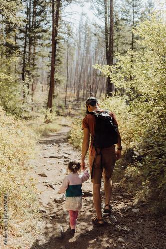 Ojciec i córka trzymając się za ręce podczas piesze wycieczki na szlak leśny