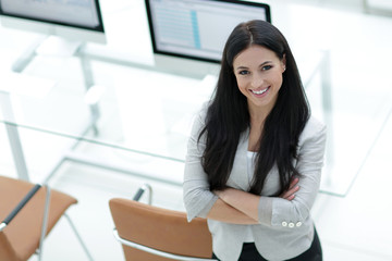 young business woman standing near modern workplace.