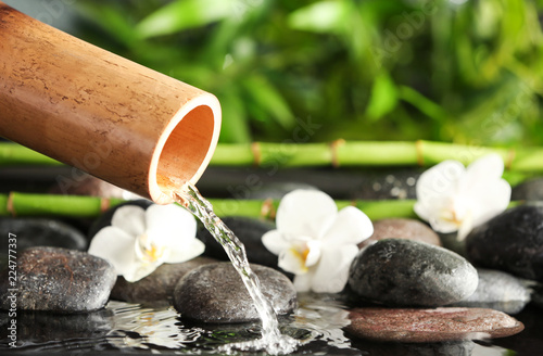 Leinwanddruck Bild Traditional bamboo fountain with spa stones and flowers, closeup. Space for text