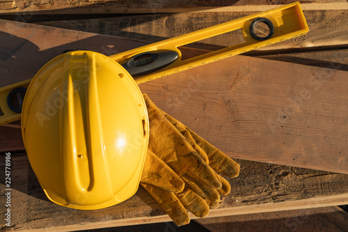 Abstract of Constrcution Hard Hat, Gloves and Level Resting on Wood Planks