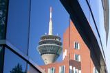 Der Fernsehturm und Geschäftsgebäude spiegeln sich im glänzenden Fenster von einem anderen Bürohaus in Düsseldorf - 224779131