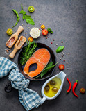 Salmon filet in old cast iron skille on dark stone background. Ingredients for making steak concept with copy space . Various herbs and seasoning rosemary ,sage leaves ,basil ,garlic and peppercorn. - 224800720