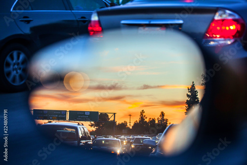 An artistic view of the busy traffic via side mirror at sunset in Los Angeles. Blurred road, headlights and rear lights of other commuters.