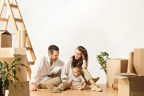 Couple moving to a new home. Happy married people with newborn child buy a new apartment to start life together. The family at repair and relocation planing to accommodation against boxes - 224825192