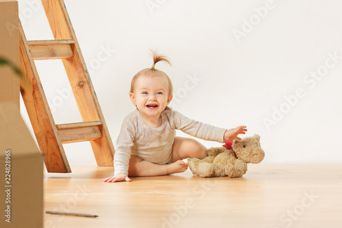 Friendly blue eyed baby girl sitting on the floor indoors at home