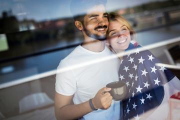 Pretty couple near window, american flag
