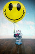 vintage robot toy holding a  yellow  happy balloon