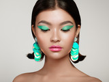 Beautiful Korean Woman with Large Turquoise Earrings. Perfect Makeup and Elegant Hairstyle. Turquoise Make-up Arrows and Pink Lipstick - 224862347
