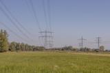 Wiese mit Hochspannungsmasten in der Landschaft - 224865515