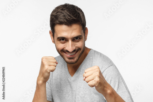 Close up portrait of smiling young man keeping his fists ready to fight and defense himself, boxing, looking at camera with smile