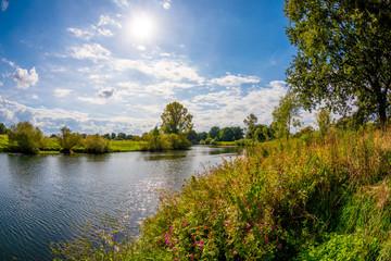 Landschaft im Sommer mit Fluss, Bäumen und Wiesen bei strahlendem Sonnenschein