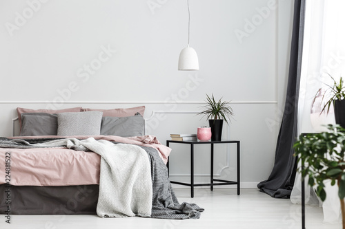Leinwandbild Motiv Warm blankets and gray pillows on a cozy double bed with dirty pink sheets by an empty wall of a white bedroom interior
