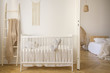 Leinwanddruck Bild - Wooden crib with cushions standing in real photo of white kid room interior with blanket on ladder and macrame on the wall