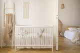 Wooden crib with cushions standing in real photo of white kid room interior with blanket on ladder and macrame on the wall