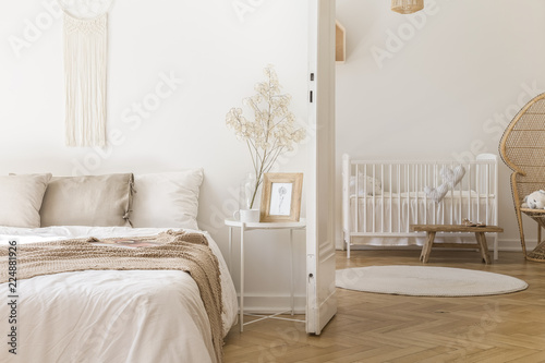 Leinwandbild Motiv White metal bedside table with decor and coffee mug placed by the bed in bright bedroom interior with door to newborn baby room with crib