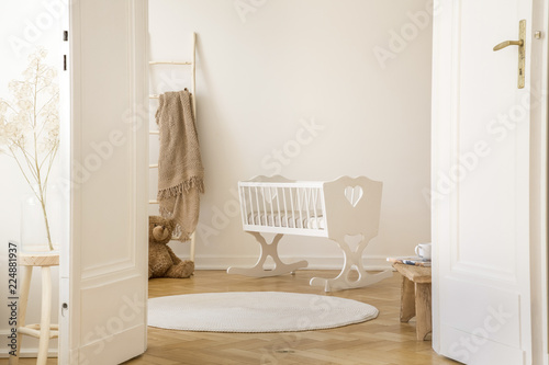 Real photo of white cradle with heart standing in Scandi kid room interior with teddy bear, herringbone parquet and empty wall with place for your poster