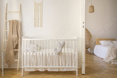 Leinwanddruck Bild Wooden crib with cushions standing in real photo of white kid room interior with blanket on ladder and macrame on the wall